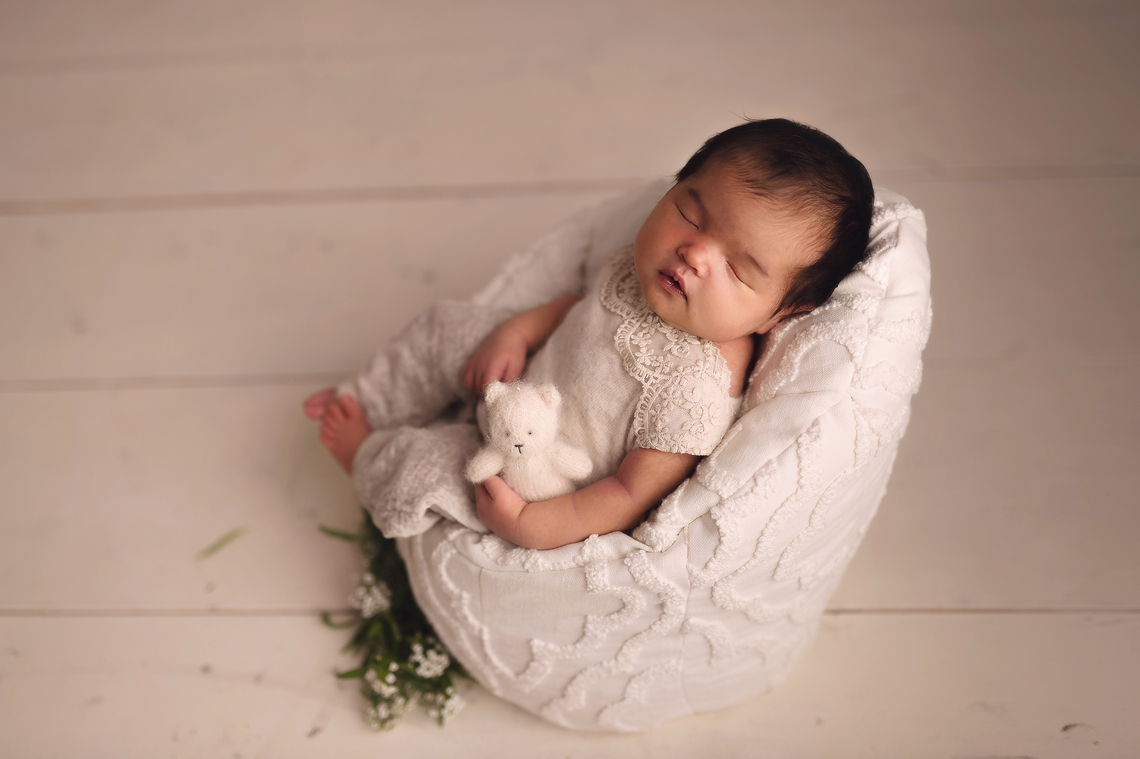 Newborn baby girl in the posing chair holding bear toy