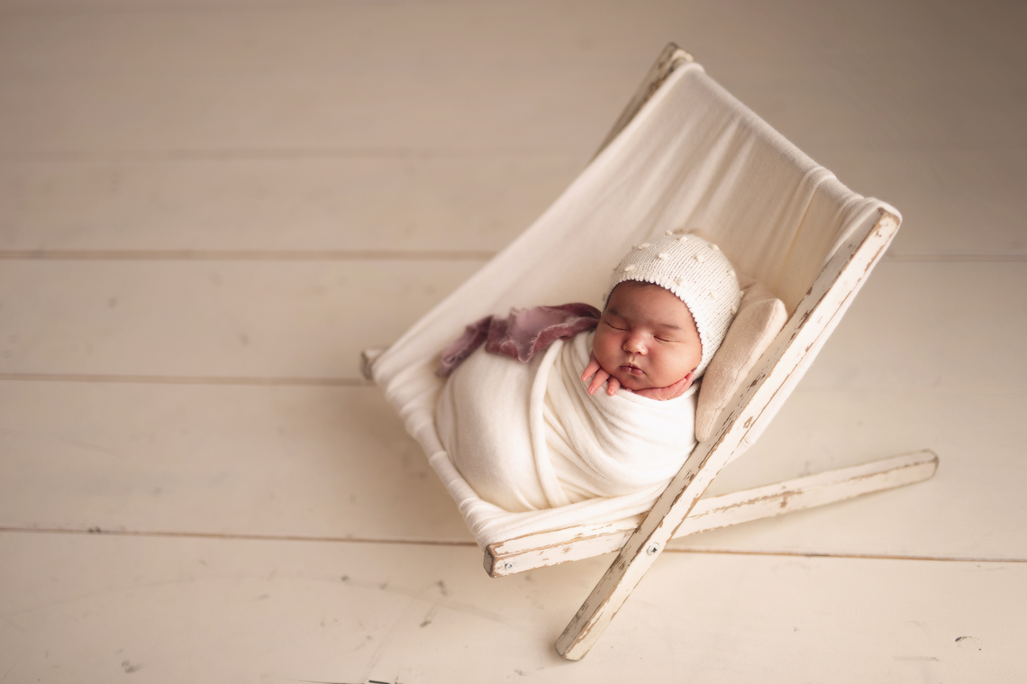 Newborn baby girl in the stool prop