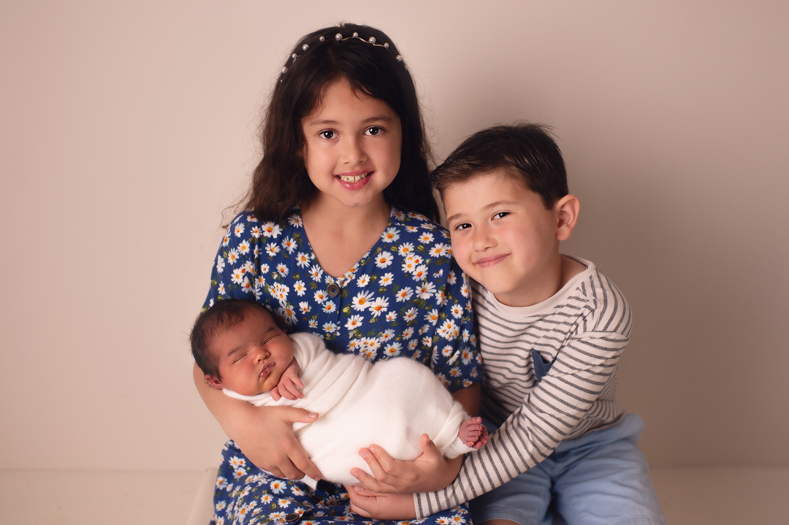 brother and sister holding a newborn baby