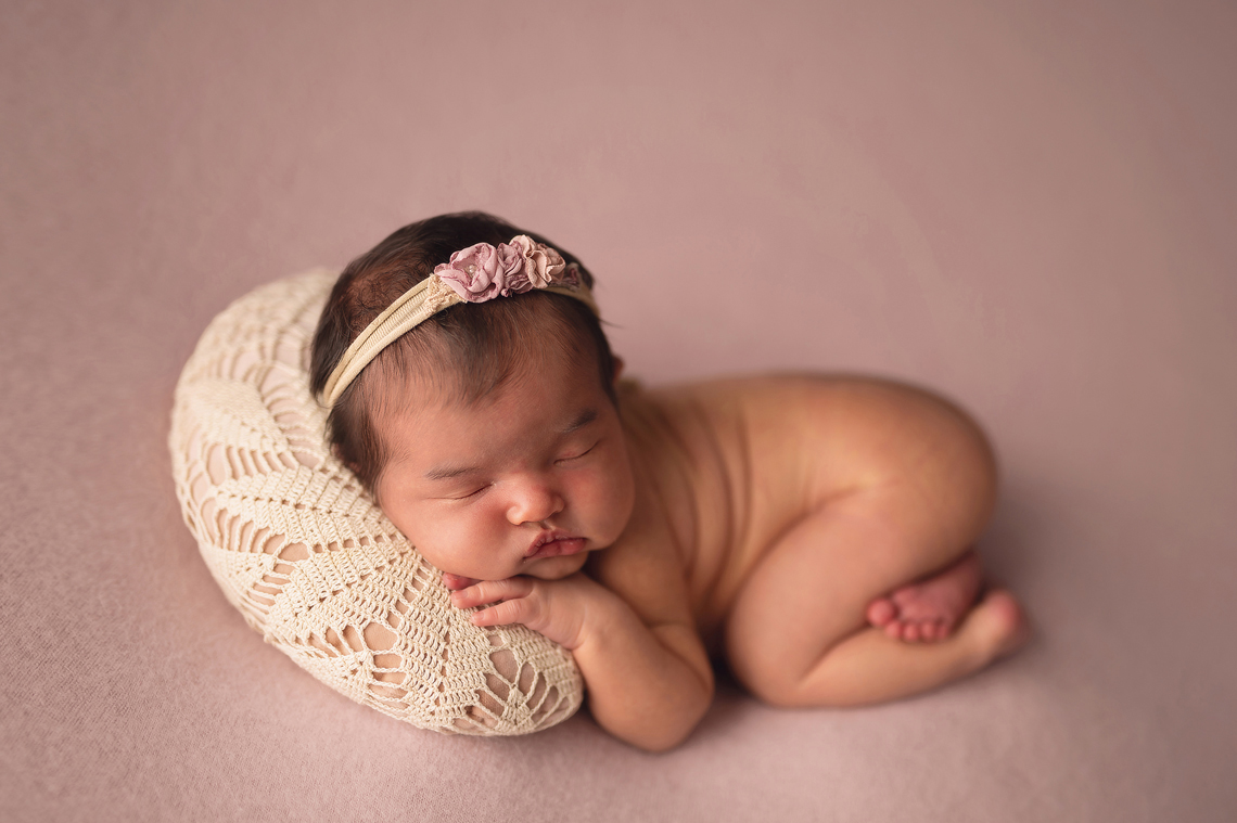 newborn baby girl on the pink background