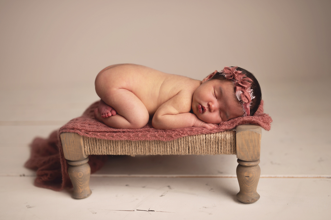 newborn baby girl sleeping on the hand made bench prop