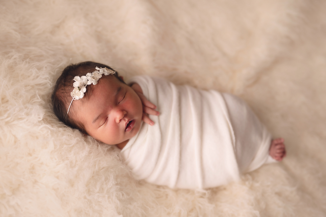 newborn baby girl wrapped in white fur