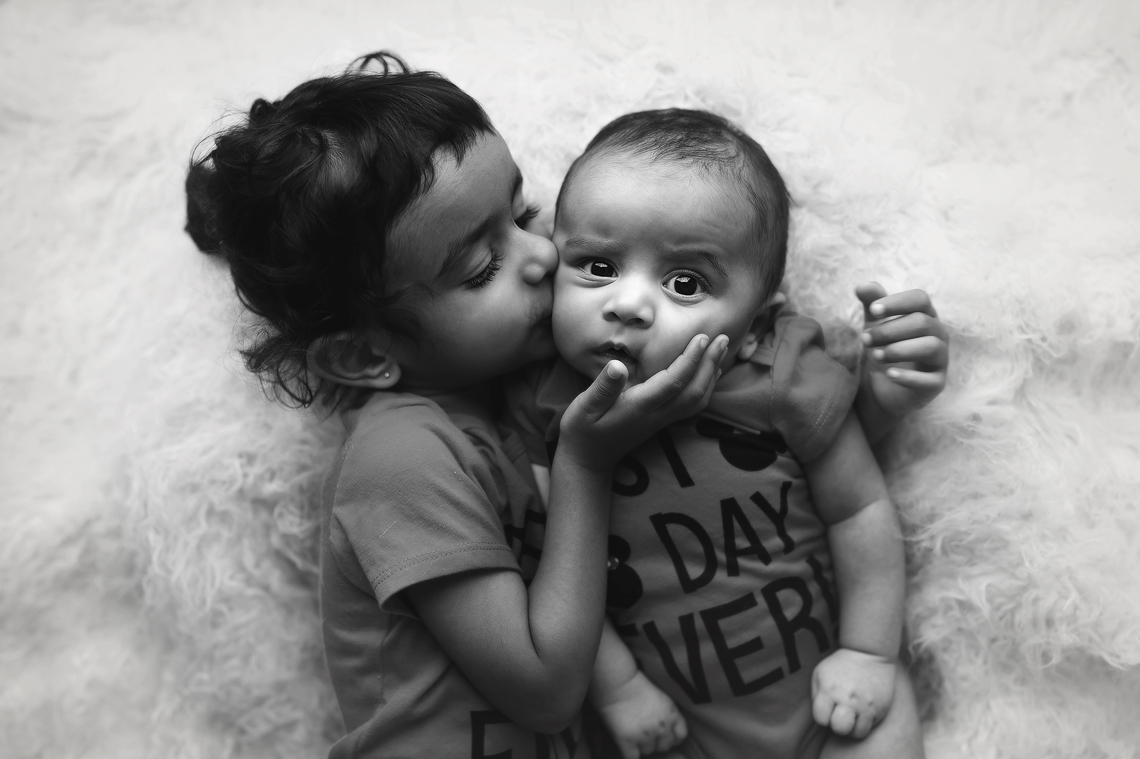 sister kissing baby brother photo