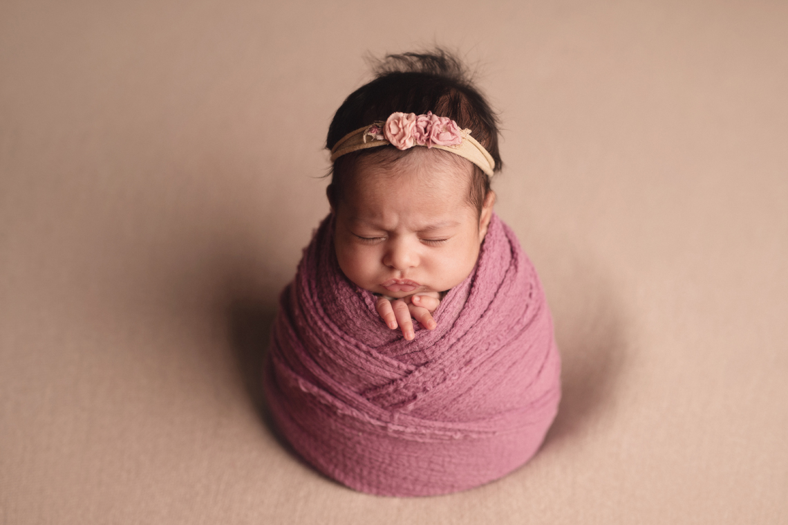 indian seven weeks old baby girl wrapped in pink fabric