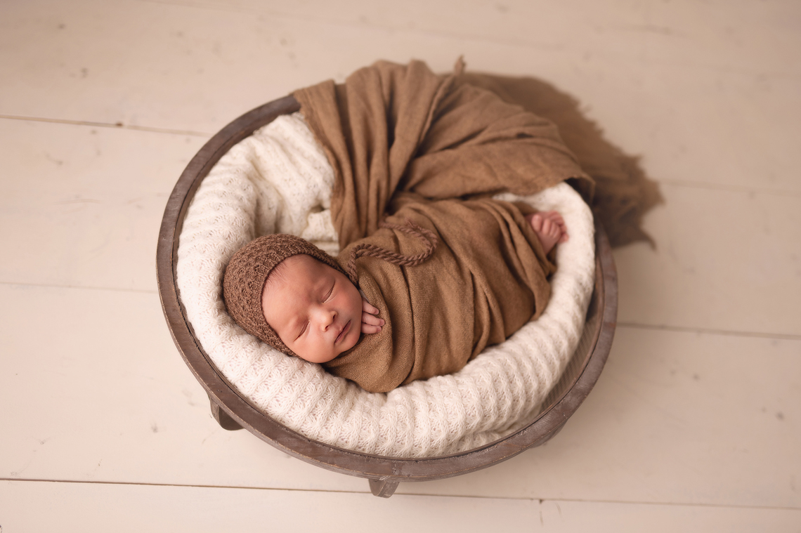 newborn baby boy in the prop in beige color