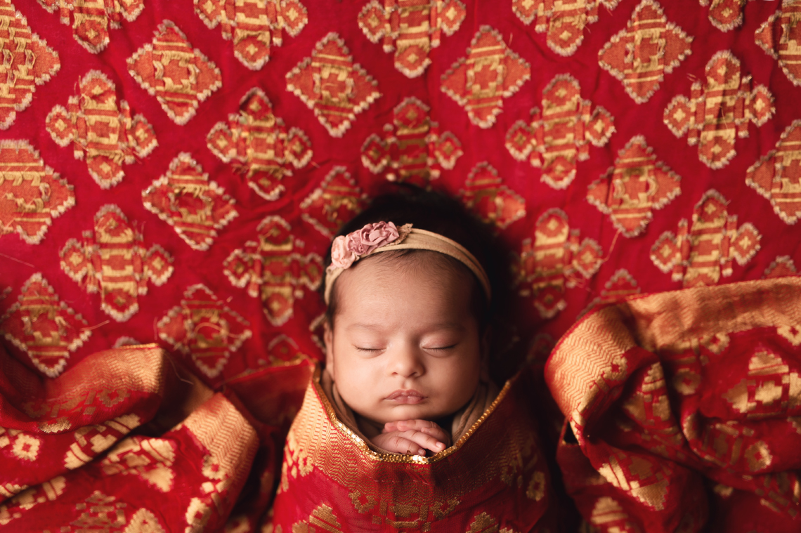 indian seven weeks old baby girl wrapped in all red fabric
