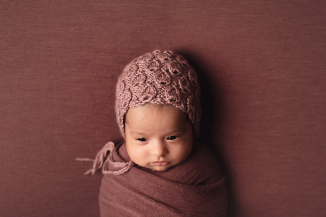 indian seven weeks old baby girl wrapped in fabric and wearing knitted hat