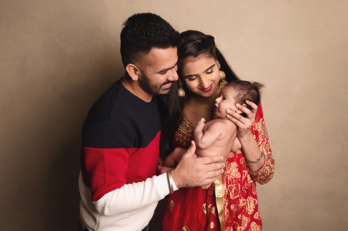 Indian family mama and dad holding seven weeks old baby girl