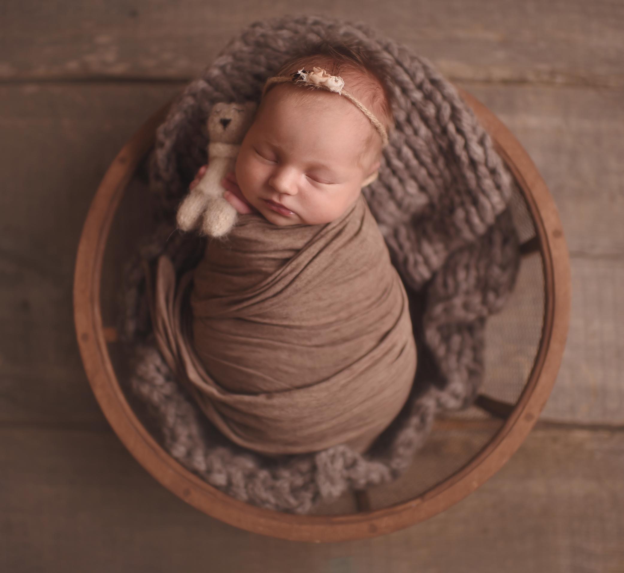 newborn baby girl in the wooden basket