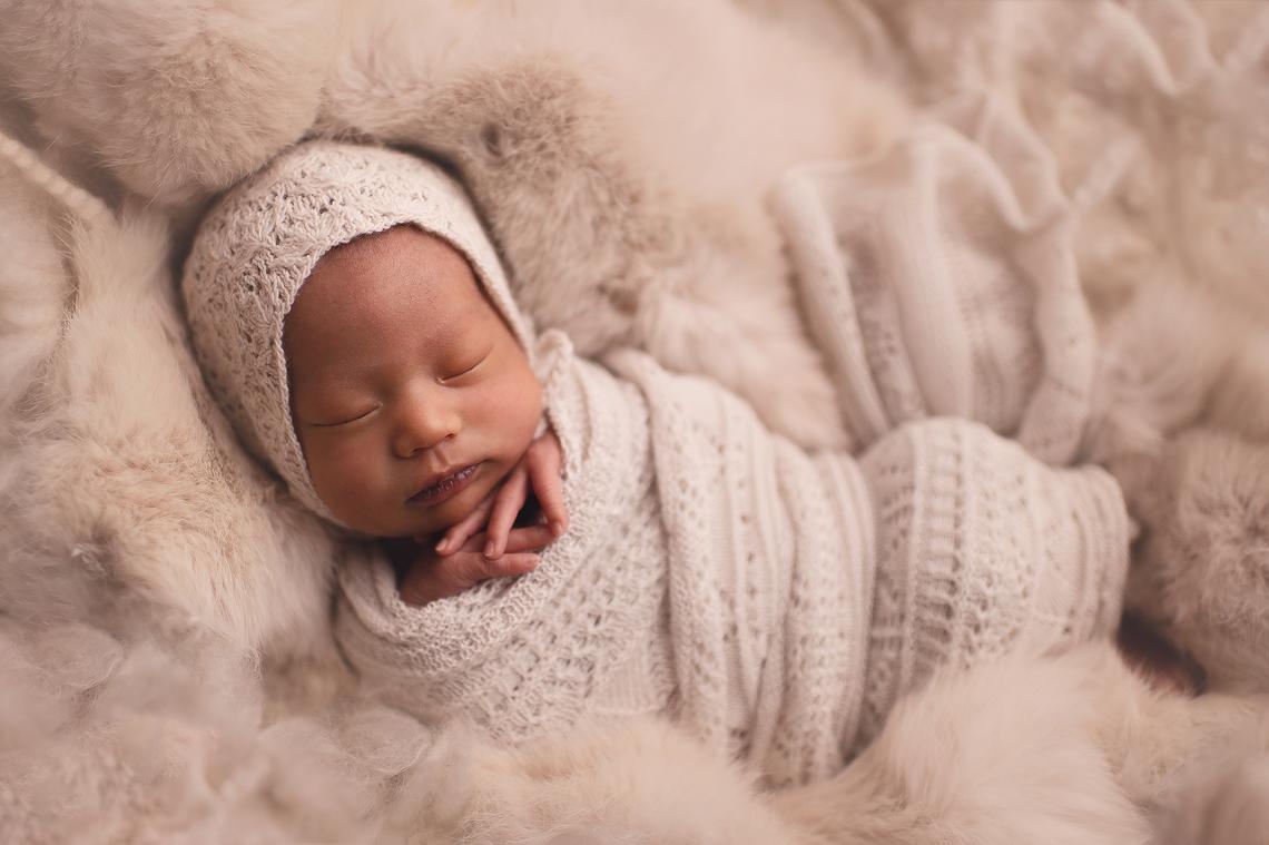 newborn baby girl sleeping with hands under the chin